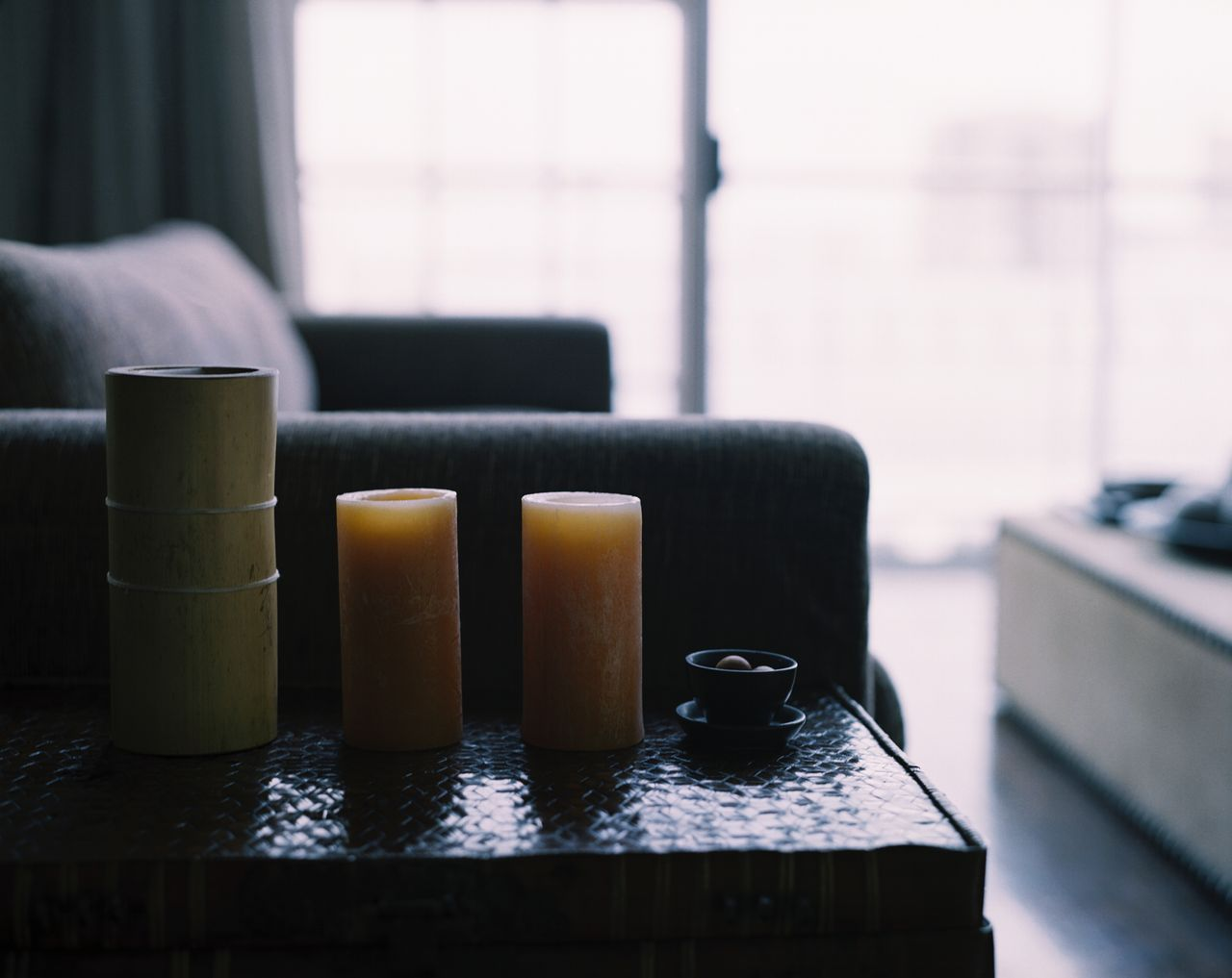 close-up of an array of decorative candles kept on a side table in a living room